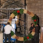 Preparing to hang the wreath in the Romanesque Hall.